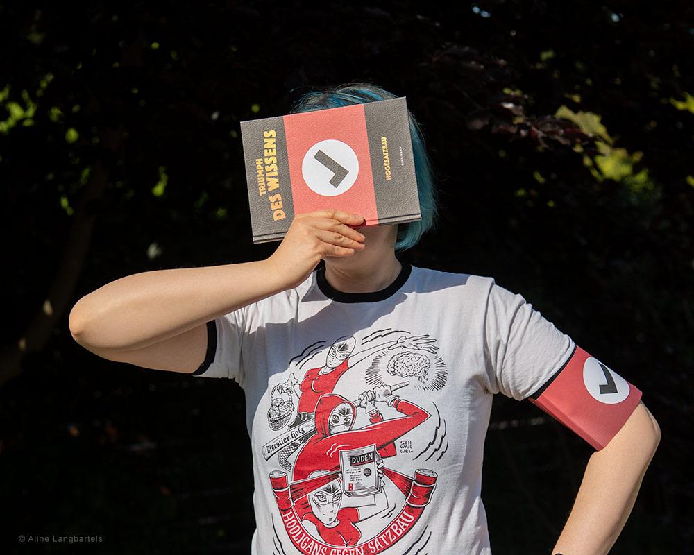 Frau mit Buch, Shirt und Armbinde HoGeSatzbau