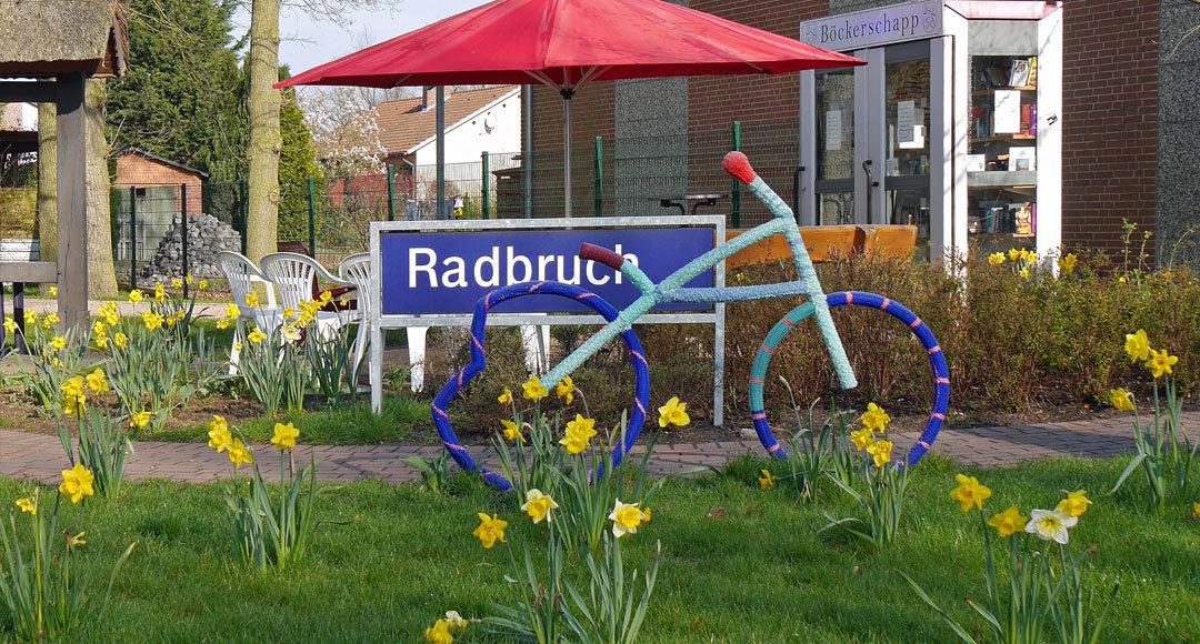 Fahrradstatue umhäkelt mit Narzissen davor und Radbruchschild dahinter